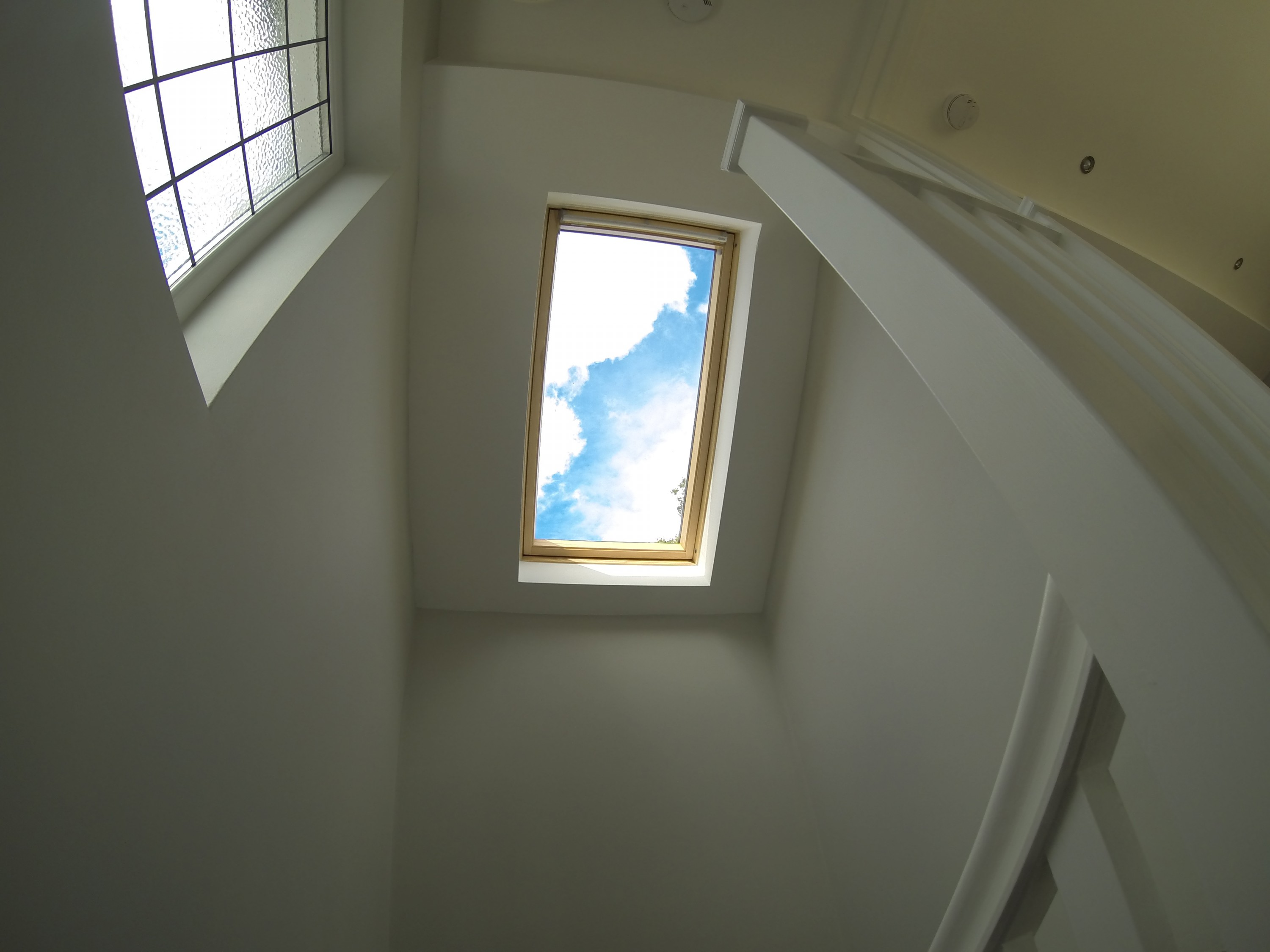 Roof window and gable wall window flooding the stairwell with light